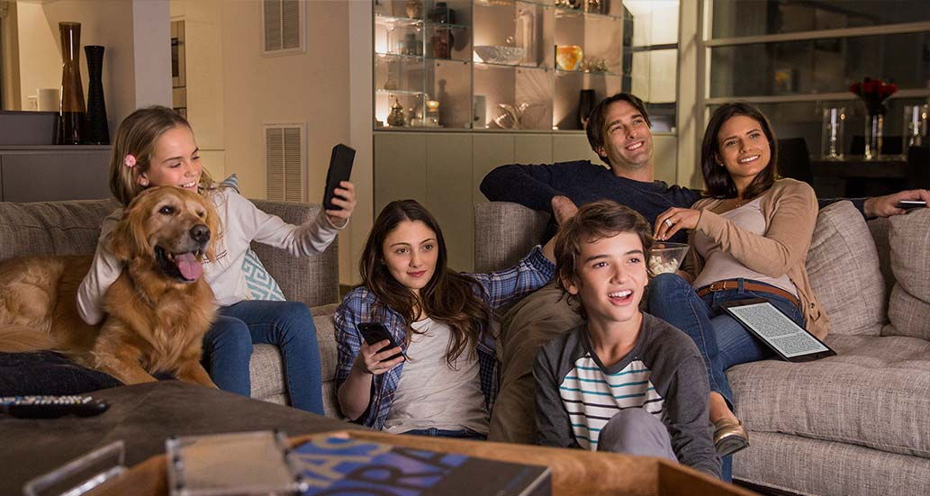 a family relaxing together while using many different devices, including phones, tablets, and e-readers