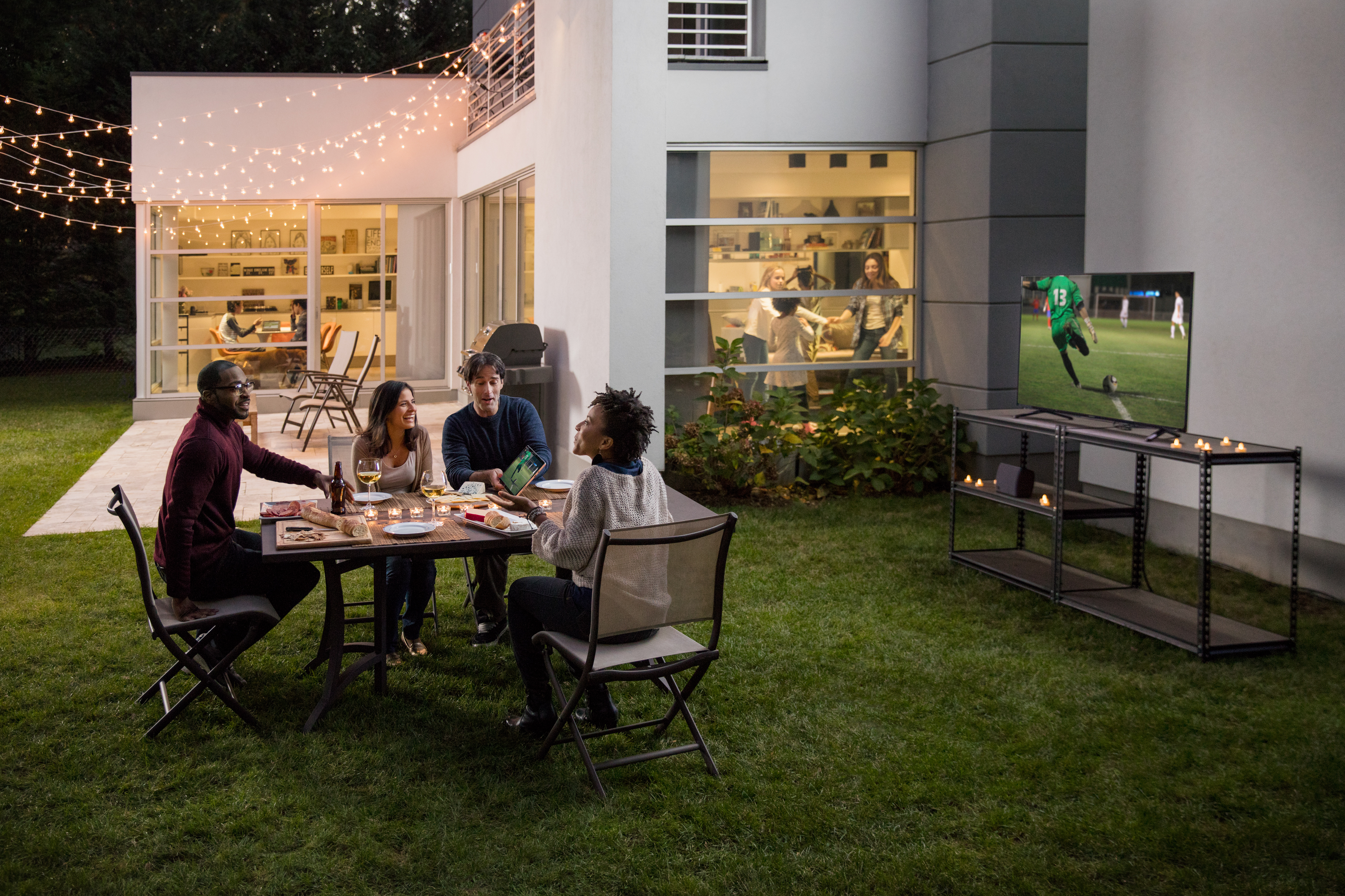 two couples at dinner in the backyard, looking at something funny on a tablet