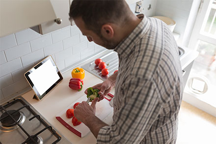Man chopping vegetables while connecting to his tablet