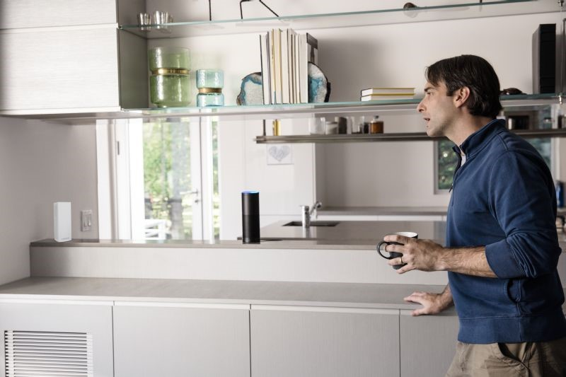 Man in kitchen next to Amazon Alexa and Velop MX4200